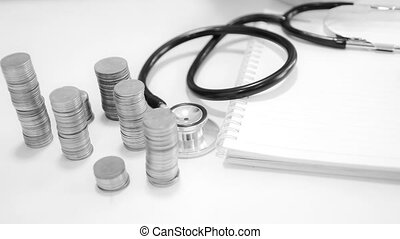 4K Time lapse of Money coins stacked decrease with stethoscope