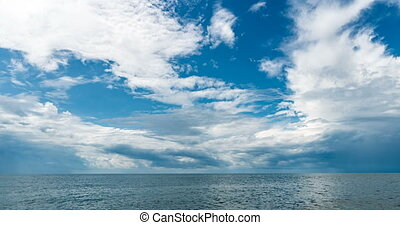 4k time lapse of the sea and blue sky, white clouds evolve ...