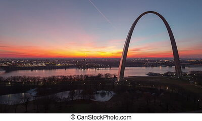 4K Time lapse aerial park view St Louis Gateway Arch at sunrise with boat traffic on the river