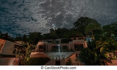 4K TimeLapse -night sky with clouds over the houses. Abstract night time lapse of Hotel, showing stars, clouds, moon, and heaven.