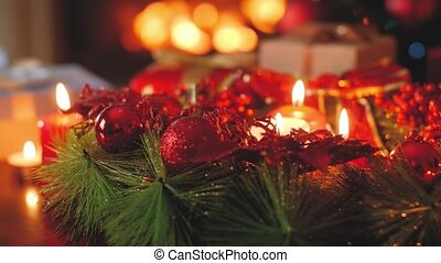 4k toned footage of burning candles, advent wreath and Christmas gifts against burning fire in fireplace at living room