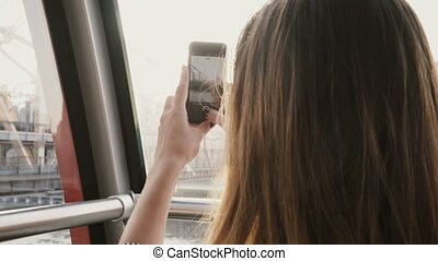 4K Tourist girl taking photos from air tram cabin. Pretty smiling European lady takes photographs in island tramway.