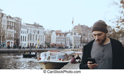 4K Tourist man walking with smartphone, Amsterdam. Casual handsome bearded smiling man walks near a river embankment.