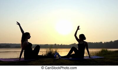 4k - Two Women Sit Doing Yoga Eagle Exercise at Sunset on a Lake Coast