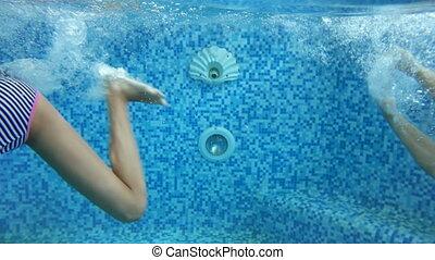 4k underwater footage of two girls diving in indoor swimming pool