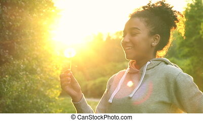 African American girl teenager or young woman laughing, smiling and blowing a dandelion at sunset or sunrise