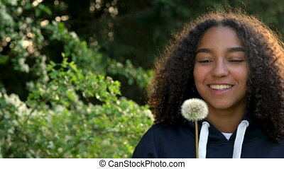 mixed race African American girl teenager or young woman laughing, smiling and blowing a dandelion at sunset or sunrise