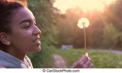 African American girl teenager or young woman laughing, smiling and blowing a dandelion