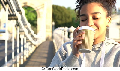 4K video clip of beautiful mixed race African American girl teenager young woman on a bridge over a river, drinking takeout coffee smiling, laughing and looking to camera