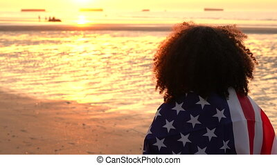 African American girl teenager female young woman wrapped in an American US Stars and Stripes flag, watching people playing on a beach at sunset or sunrise