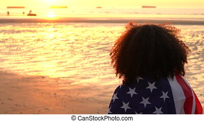 4K video clip of mixed race African American girl teenager female young woman wrapped in an American US Stars and Stripes flag watching people having fun on a beach at sunset or sunrise