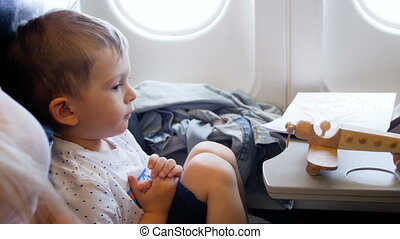 4k video little toddler boy looking at woodent airplane toy...