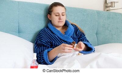 4k, video, od, młoda kobieta, w, kąpielowy szlafrok, czuły chory, cyganiąc w łóżku, i, picie, pigułki