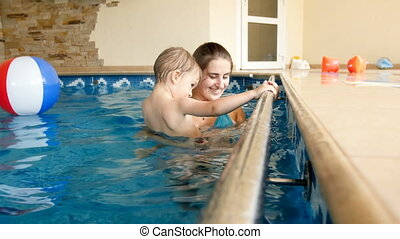 4k video of 3 years old toddler boy with young mother in swimming pool at gym