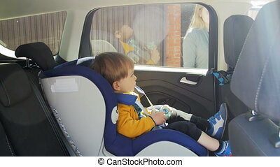 4k video of adorable baby boy sitting in child car safety...