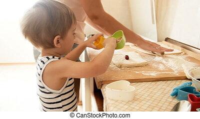 4k video of adorable toddler boy making cookies with mother on kitchen wooden countertop