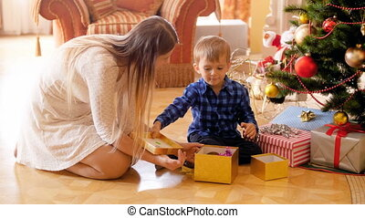 4k video of adorable toddler boy sitting on floor with mother under Christmas tree and opening gift box with presents