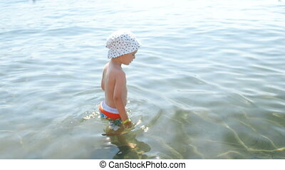 4k video of adorable toddler boy standing at sea at hot sunny day