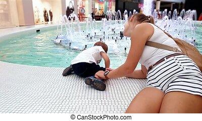 4k video of adorable toddler boy touching water in beautiful...