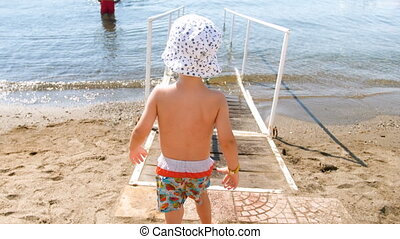 4k video of adorable toddler boy walking in sea on wooden ramp at sunny day