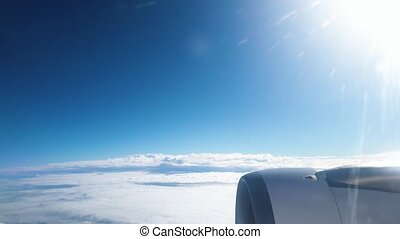 4k video of airplane engine and wing flying above the clouds in clear blue sky