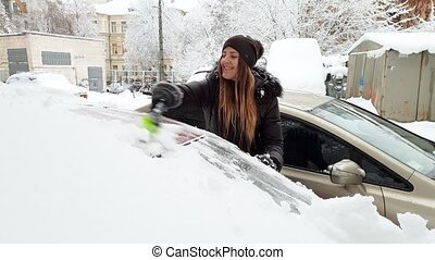4k video of beautiful female driver cleaning her car from...