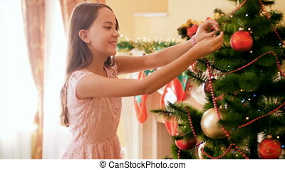 4k video of beautiful smiling girl decorating Christmas tree...