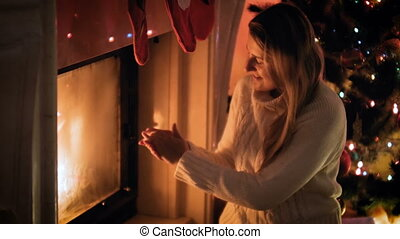 4k video of beautiful smiling woman in woolen sweater warming at burning fireplace at night