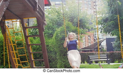 4k video of beautiful smiling woman riding on swing at playground