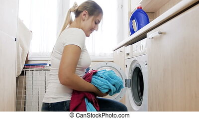 4k video of beautiful smiling woman putting dirty clothes in...