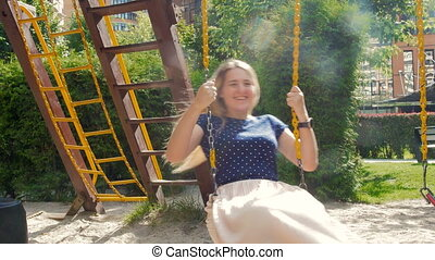4k video of beautiful smiling woman with long hair riding on swing at playground
