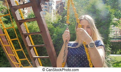 4k video of beautiful smiling woman with long hair riding on swing at playground at park