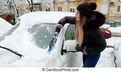 4k video of beautiful smiling young woman removing snow from...