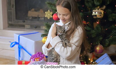 4k video of beautiful teenage girl caressing cute kitten...
