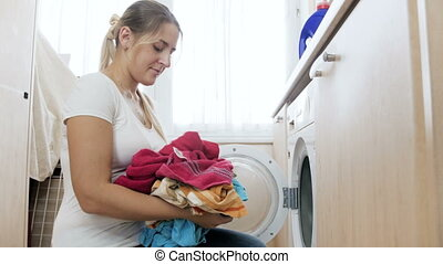 4k video of beautiful young housewife loading and turning on washing machine