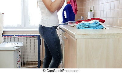 4k video of beautiful young woman doing housework in laundry...