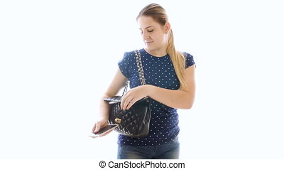 4k video of beautiful young woman takes smartphone out of handbag against white background