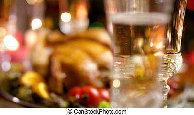 4k video of camera focusing on baked chicken for Christmas and bubbles in glass of champagne