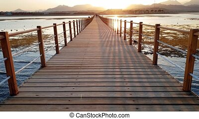 4k video of camera moving along long wooden pier in the...