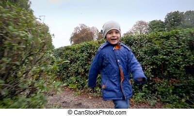 4k footage of cheerful smiling boy running in bush labyrinth or maze in the garden at park