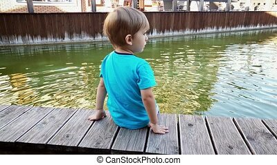 4k video of chererful smiling toddler boy sitting on the...
