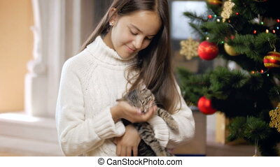 4k video of cute kitten and teenage girl playing under Christmas tree at house