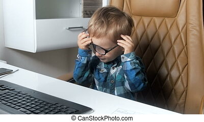 4k video of cute smiling little boy sitting in office chair...