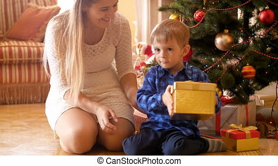 4k video of cute smiling toddler boy sitting under Christmas tree with mother and shaking gift boxes with presents