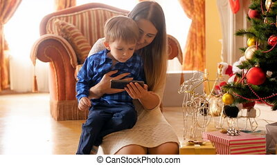 4k video of cute toddler boy watching cartoons with mother under Christmas tree