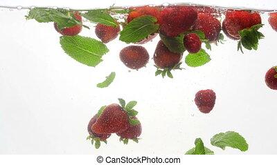 4k video of fresh ripe strawberries, raspberries and mint...