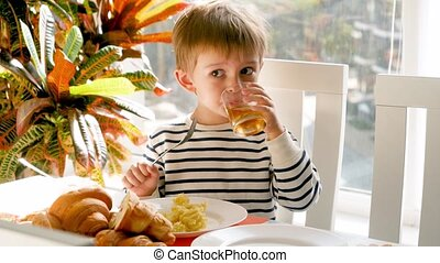 4k video of funny little boy having lunch in dining room and...
