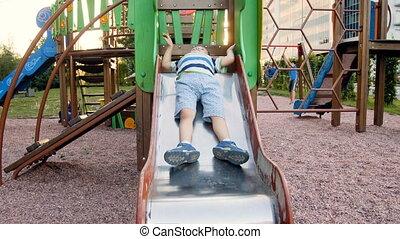 4k video of funny little toddler boy sliding down on slide at playground