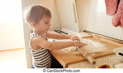 4k video of funny toddler boy rolling pie dough with big wooden rolling pin on kitchen countertop