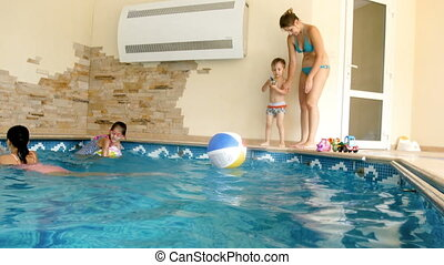4k video of happy family having fun and playing at indoor swimming pool at hotel